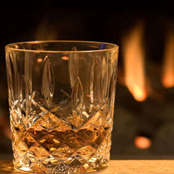 Christmas whisky glass by fire